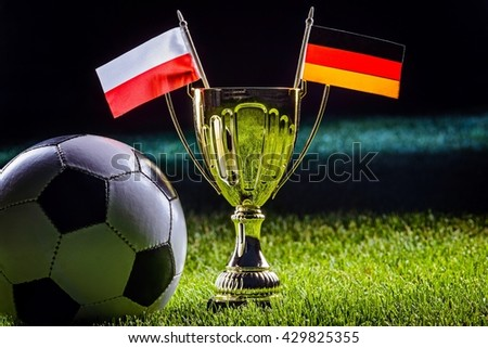 Football cup and Polish and German flags with football ball on grass by night - stock photo