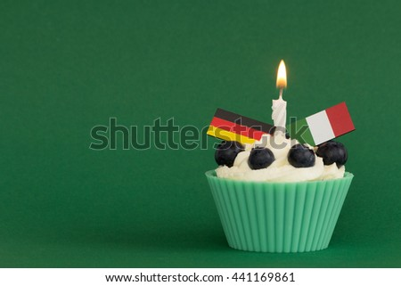 football cupcake Germany against Italy with burning candle and green background - stock photo
