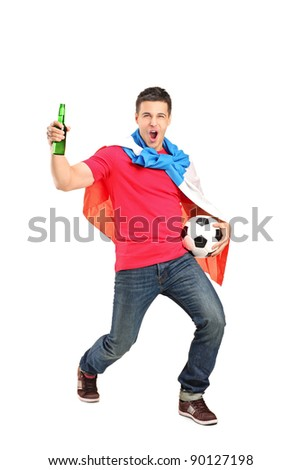Football fan covered with dutch flag and holding a beer bottle and football cheering isolated on white background
