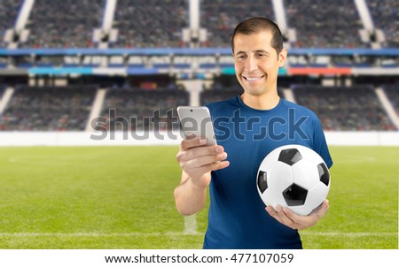 football fan holding the ball and betting in internet with the smart phone at empty stadium in background