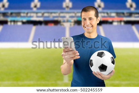 football fan holding the ball and betting in internet with the smartphone at empty stadium in background
