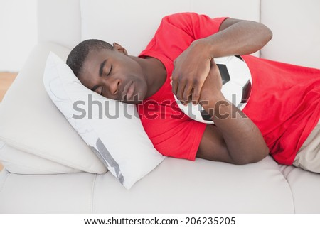 Football fan sleeping on couch hugging ball at home in the living room - stock photo