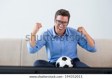 Football fan watching game at home - stock photo