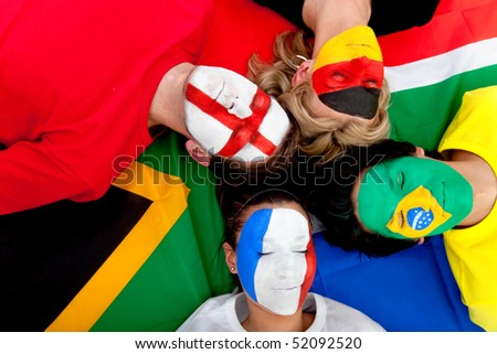 Football fans with painted faces lying on the South African flag - isolated over a white background - stock photo