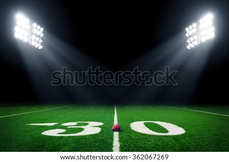 Football field at night with stadium lights