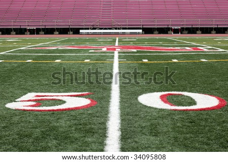 Football field view on 50 yard line with spectator stands - stock photo