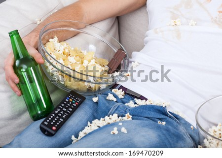 Football fun on a couch with his set - stock photo