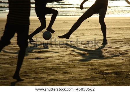 football game on the beach  against the sun - stock photo