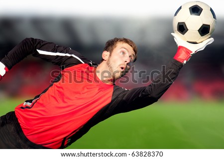 Football goalkeeper at a stadium catching the ball - stock photo