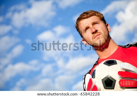 Football goalkeeper with a ball in his hands outdoors - stock photo