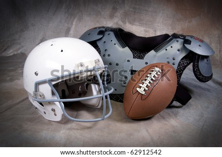 Football helmet and shoulder pads on tan background - stock photo