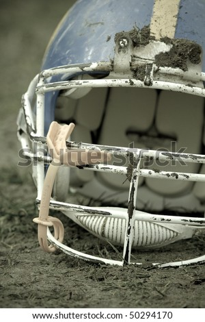 Football helmet covered with mud - stock photo