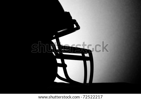 Football Helmet - This is a black and white silhouette shot of a football helmet. - stock photo