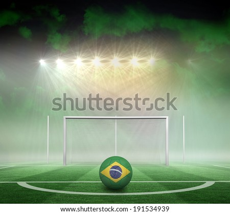 Football in brasil colours against football pitch under spotlights - stock photo