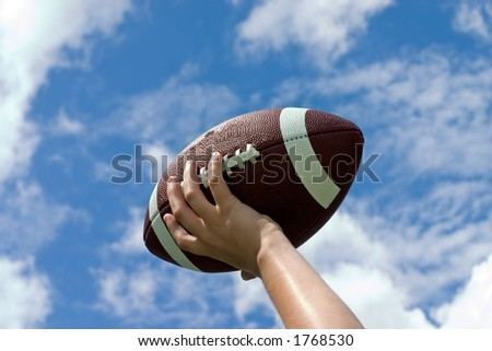 Football in child's hand against blue sky with puffy clouds - stock photo