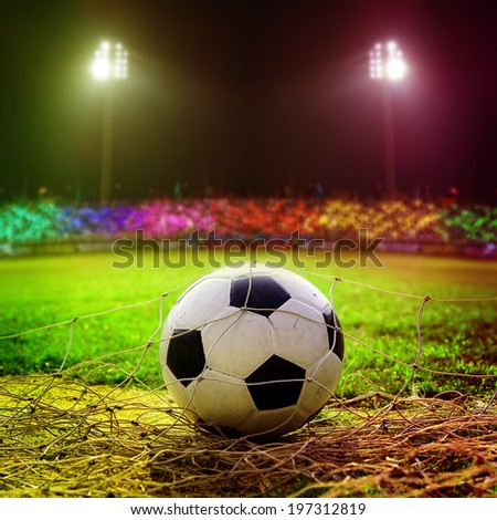 Football in goal net with stadium light - stock photo