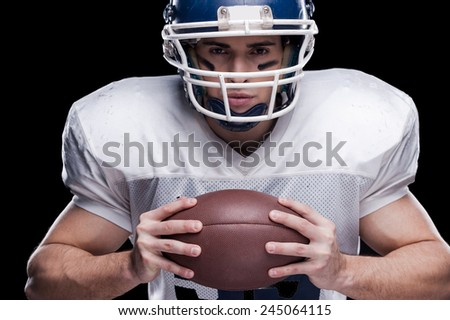 Football is my life!  American football player looking at camera and holding ball while standing against black background  - stock photo