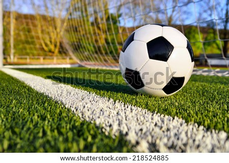 Football lying on the green soccer pitch behind the goal line - stock photo