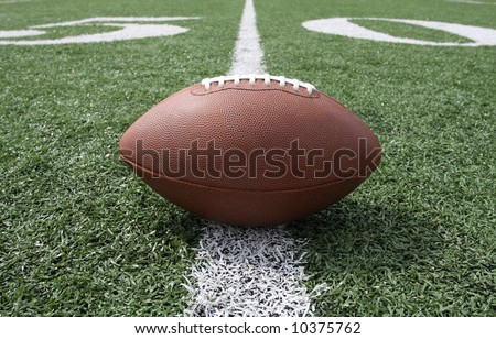 Football near the 50 yard line - stock photo