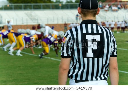 Football official with black and white striped jersey, symbol is for field judge, at an american football game - stock photo