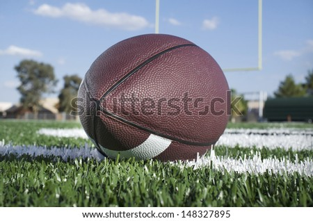 Football on field with goal post in background - stock photo