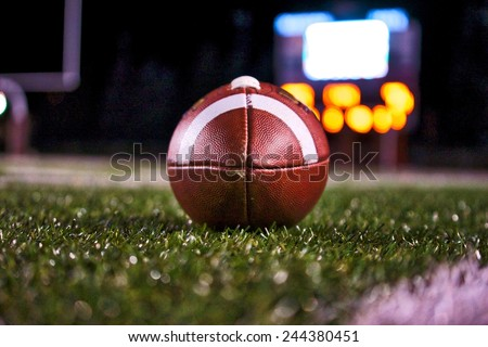 Football on Field with Scoreboard - stock photo