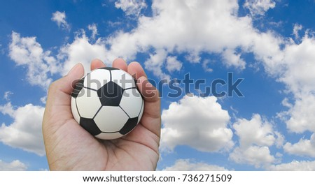 Football on hand blue sky background copy space. Football sport game concept