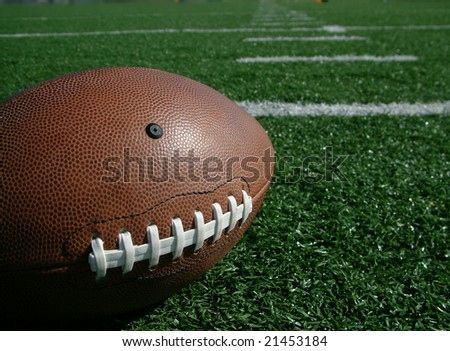 Football on hash marks of high school turf football field - stock photo