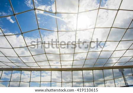 Football or soccer empty goal, net, blue sky and sun in the background. sport backdrop.  - stock photo