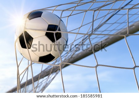 Football or soccer goal, with a neutral design ball flying into the net, blue sky and sun in the background - stock photo