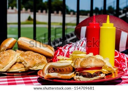 Football party with cheeseburger, hot dog, potato chips, pom poms, buns, and football.  Football field in background. - stock photo