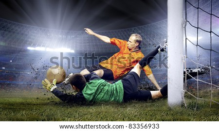 Football player and jump of goalkeeper on the field of stadium at night - stock photo