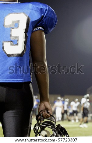 Football player at the side line watching the game. - stock photo
