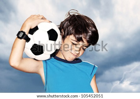 Football player celebrate victory, cute boy playing on stadium, kid enjoying team game outdoor, teen holding catching ball, happy child facial expression, sport fan portrait over cloudy sky background - stock photo