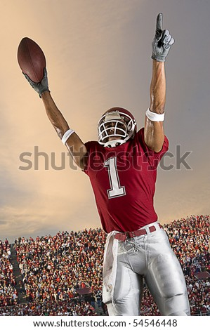 Football player celebrates after scoring a touchdown. Vertical shot. - stock photo