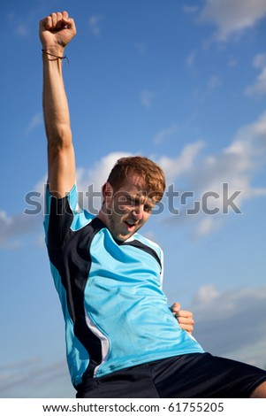 Football player celebrating with arms up outdoors - stock photo