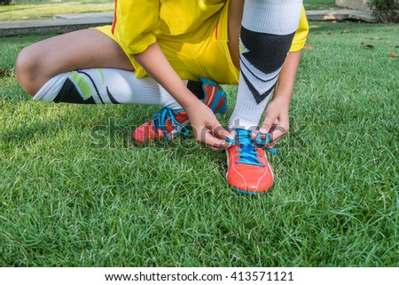 Football player getting ready for the game tying his shoes.