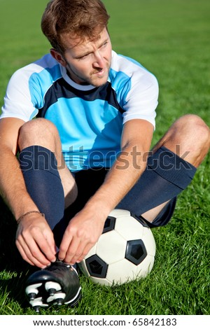 Football player getting ready for the game tying his shoes - stock photo