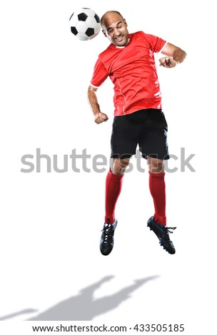 football player in action jumping for head kick in red soccer jersey and socks with black shorts isolated on white background