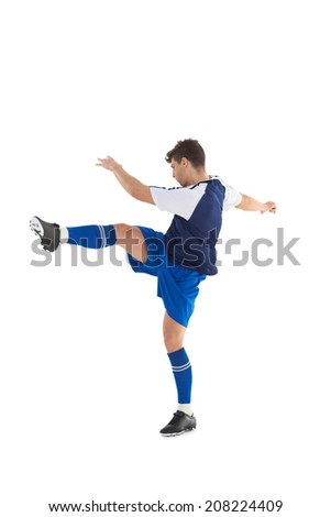 Football player in blue jersey kicking on white background - stock photo