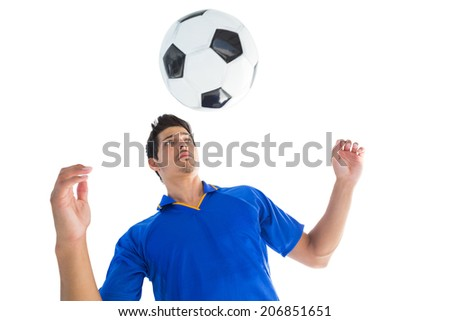 Football player in blue jumping to ball on white background