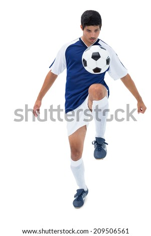Football player in blue kicking ball on white background - stock photo