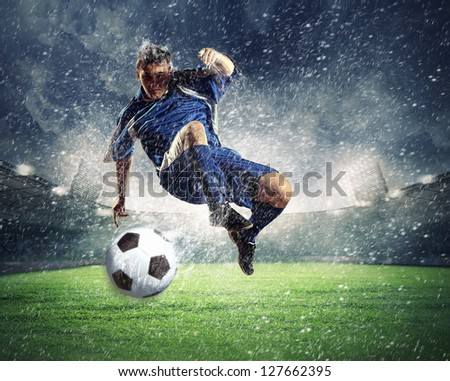 football player in blue shirt striking the ball aloft at the stadium under the rain - stock photo