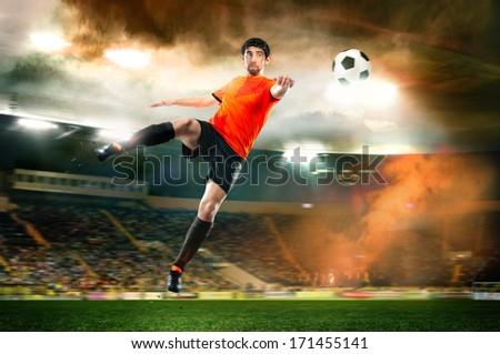football player in orange shirt striking the ball at the stadium - stock photo
