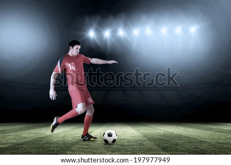 Football player in red kicking against football pitch under spotlights