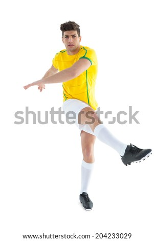Football player in yellow jersey kicking on white background - stock photo