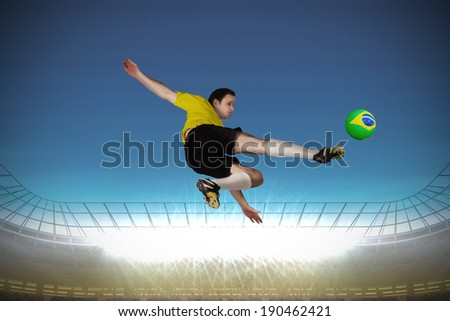 Football player in yellow kicking against large football stadium with spotlights under bright blue sky