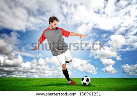 Football player kicking a ball in the field - stock photo