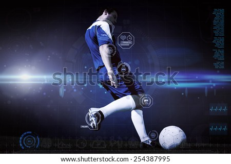 Football player kicking ball against blue dots on black background - stock photo
