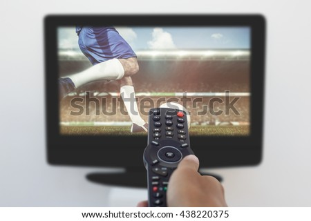 Football player kicking ball against hand holding remote and changing channel